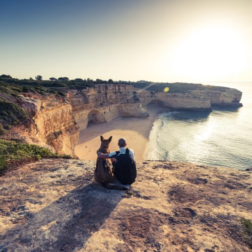 Best friends travellers sitting at cliffs in Portugal at sunset.